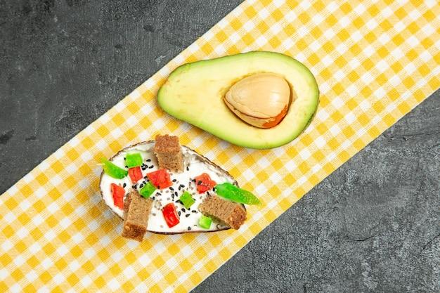 Top view of creamy avocados with fresh avocado on dark grey surface