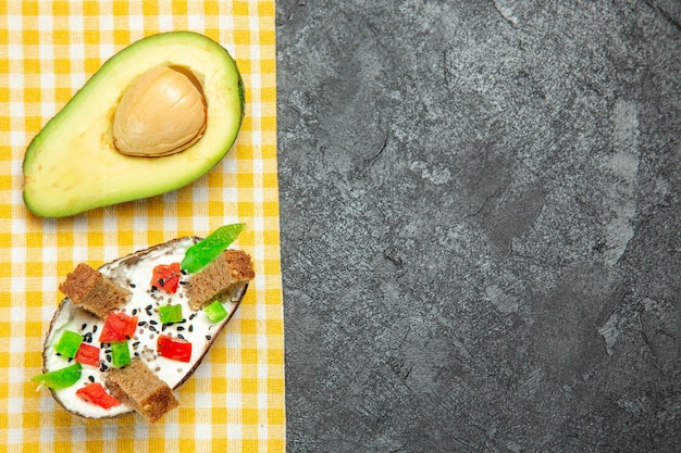 Top view of creamy avocados with fresh avocado on grey surface