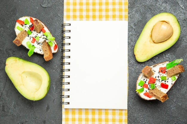 Top view of creamy avocados with fresh avocados on dark grey surface