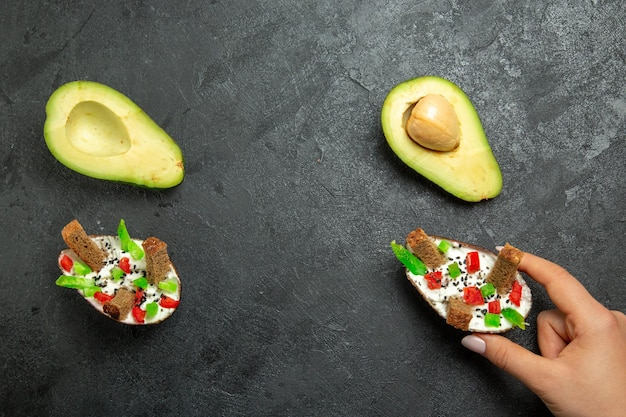 Top view of creamy avocados with fresh avocados on grey surface