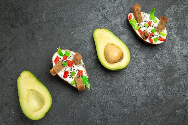 Top view of creamy avocados with fresh avocados on the grey surface