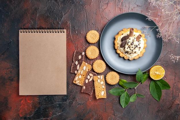 ダークテーブルの甘いケーキのデザートにクッキーとパイのスライスとクリーミーなケーキの上面図