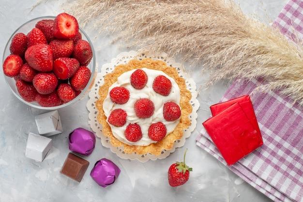 Vista dall'alto della torta cremosa con fragole rosse fresche e torta di caramelle al cioccolato sulla scrivania a luce bianca, torta di frutta e bacche di biscotti alla crema dolce