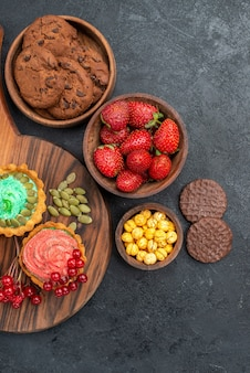 어두운 테이블 디저트 쿠키 달콤한에 과일과 비스킷이있는 상위 뷰 크림 케이크