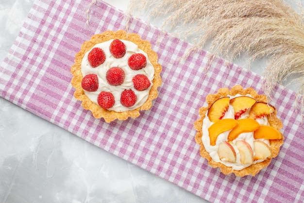 Top view of creamy cakes with white yummy cream and sliced strawberries peaches apricots on light, fruit cake cream bake