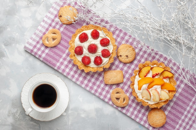 Top view of creamy cakes with white yummy cream and sliced strawberries peaches apricots with cookies on light desk, fruit cake cream bake tea