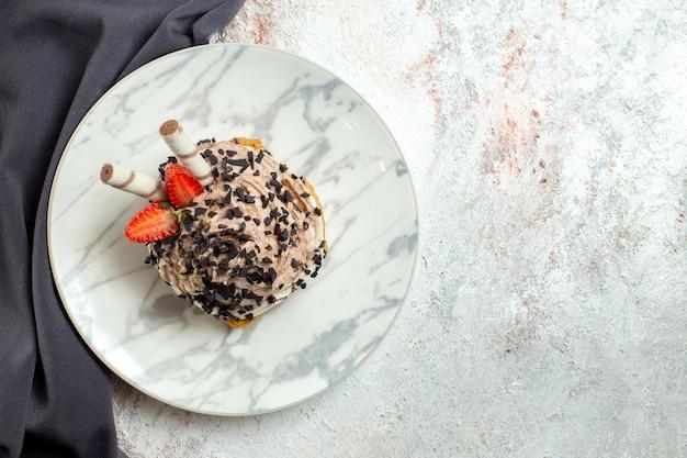 Torta cremosa e deliziosa vista dall'alto su torta di crema dolce biscotto per il tè di compleanno di superficie bianca
