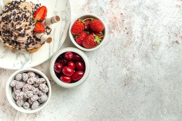흰색 표면에 신선한 과일과 함께 상위 뷰 크림 맛있는 케이크 생일 차 케이크 비스킷 달콤한 크림