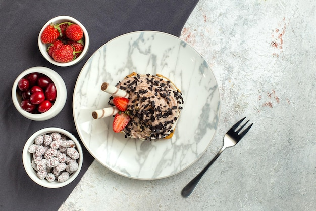 Torta cremosa e deliziosa vista dall'alto con frutta fresca su superficie bianca torta di crema dolce biscotto per il tè di compleanno white