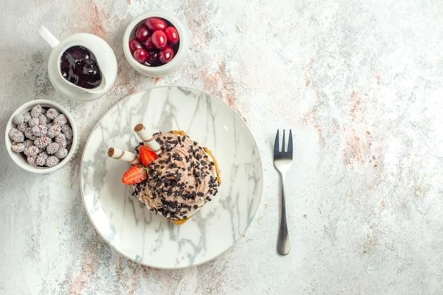 上面図白い表面にイチゴとクリーミーなおいしいケーキバースデークリームティーケーキビスケット甘い