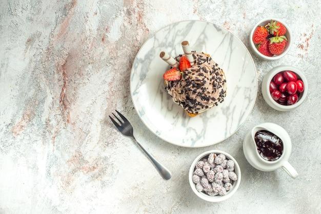 Vista dall'alto deliziosa torta cremosa con fragole su superficie bianca crema di compleanno torta di tè dolce biscotto