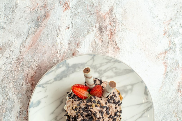 Top view creamy delicious cake with strawberries on the white surface cream tea biscuit birthday cake sweet