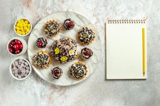 Vista dall'alto deliziose torte cremose con caramelle sulla scrivania bianca torta da tè biscotto dolce crema di compleanno