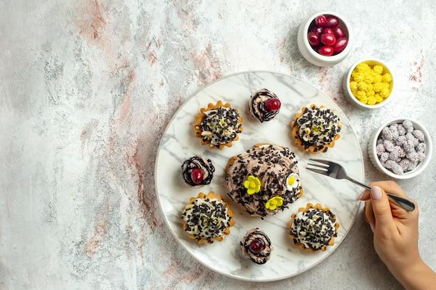 Vista dall'alto deliziose torte cremose con caramelle sulla superficie bianca torta di tè biscotto dolce crema di compleanno