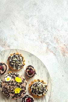 Vista dall'alto deliziose torte cremose con scaglie di cioccolato su una superficie bianca chiara torta biscotto biscotto tè crema dolce