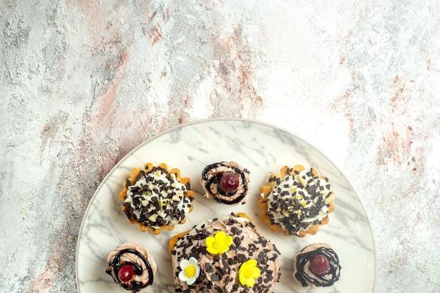 흰색 표면 케이크 비스킷 쿠키 차 달콤한 크림에 초콜릿 cips와 상위 뷰 크림 맛있는 케이크
