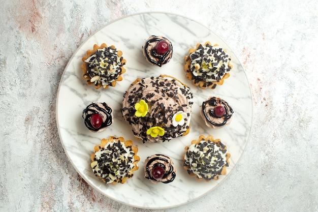 Vista dall'alto deliziose torte cremose con scaglie di cioccolato su superficie bianca torta biscotto biscotto tè crema dolce