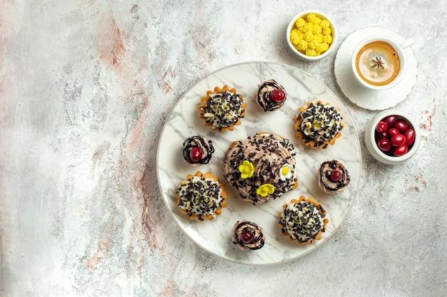 Vista dall'alto deliziose torte cremose con scaglie di cioccolato su una superficie bianca torta al tè biscotto dolce crema di compleanno