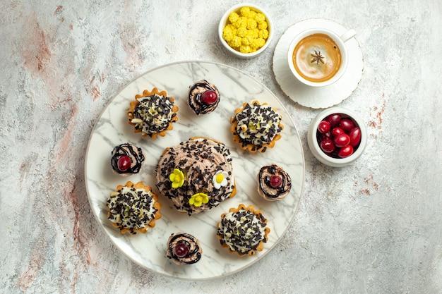 Vista dall'alto deliziose torte cremose con scaglie di cioccolato su una superficie bianca torta al tè biscotto dolce crema di compleanno Foto Gratuite