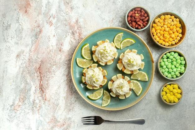 トップビュー白い表面にレモンスライスとキャンディーが付いたクリーミーでおいしいケーキビスケットクッキークリームティースイート