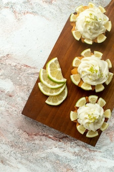 Top view creamy delicious cakes with lemon slices on a white surface cake biscuit cookie sweet tea cream