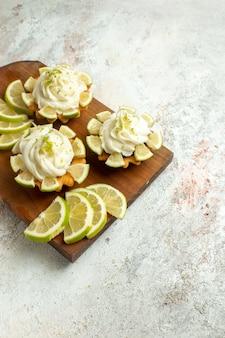 Vista dall'alto deliziose torte cremose con fette di limone su superficie bianca torta biscotti biscotti crema di tè dolce