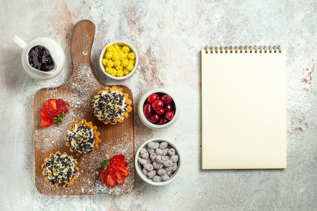 Vista dall'alto deliziose torte cremose con fragole rosse e caramelle su superficie bianca torta di tè biscotto dolce crema di compleanno