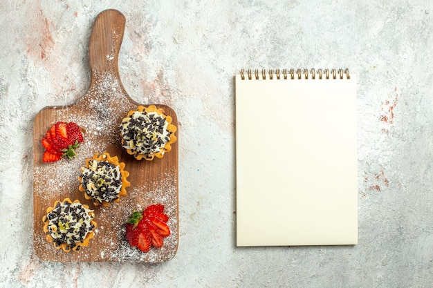 Vista dall'alto deliziose torte cremose con fragole rosse su superficie bianca torta di tè biscotto dolce crema di compleanno