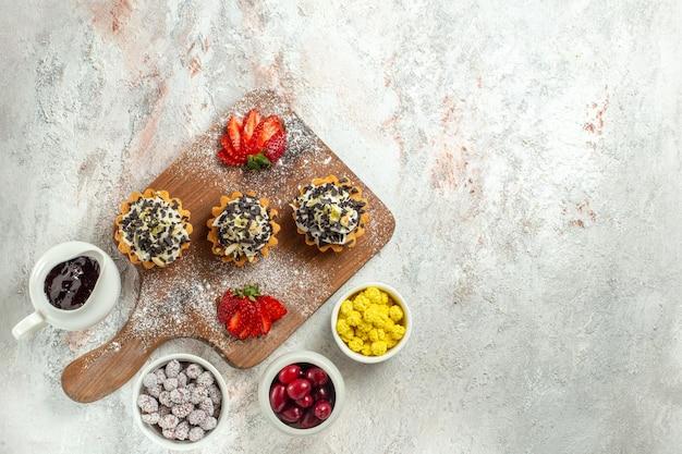 Vista dall'alto deliziose torte cremose con fragole rosse affettate su superficie bianca torta di tè biscotto crema di compleanno dolce
