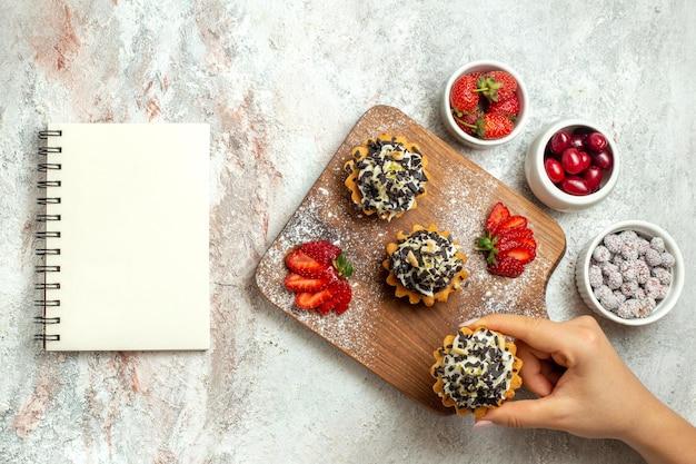 Vista dall'alto deliziose torte cremose con fragole a fette su crema di torta dolce biscotto per il tè di compleanno superficie bianca