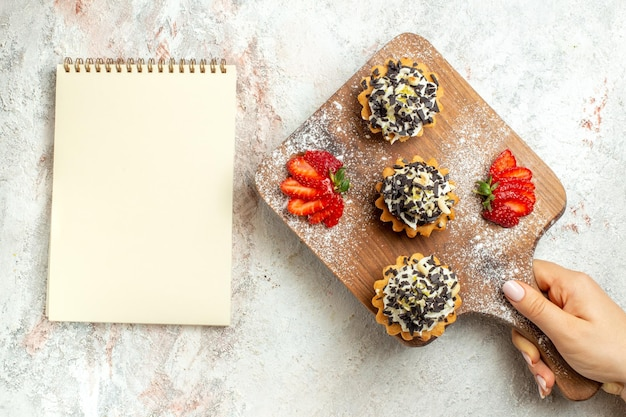 Vista dall'alto deliziose torte cremose con fragole a fette su crema di superficie bianca torta di tè biscotto dolce di compleanno