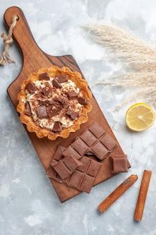 Вид сверху сливочный маленький торт с шоколадными батончиками и корицей на светлом столе сладкий торт сахарный крем шоколад