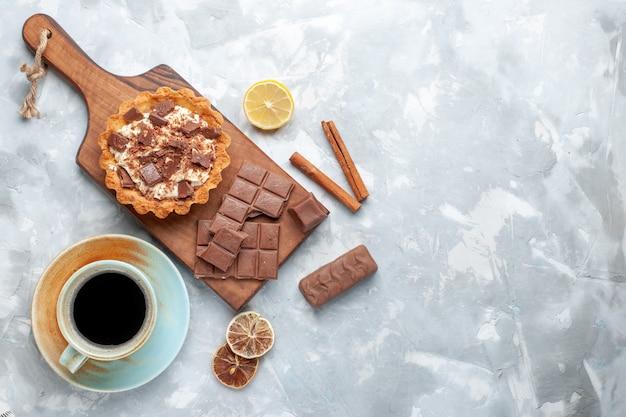 Вид сверху сливочный маленький торт с шоколадными батончиками и чаем с корицей на светлом столе сладкий торт сахарный крем шоколад