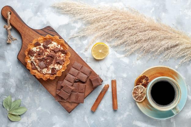 Вид сверху сливочный маленький торт с шоколадными батончиками и чаем на светлом столе сладкий торт сахарный крем шоколад