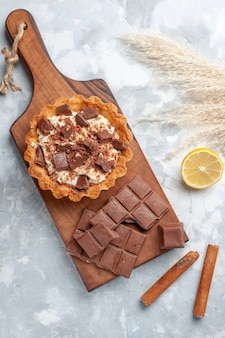 Torta cremosa vista dall'alto con barrette di cioccolato e cannella sulla scrivania leggera torta dolce crema di zucchero al cioccolato