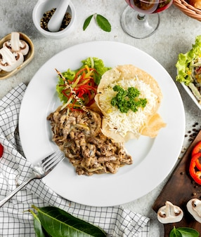 Top view of creamy meat slices with mushroom served with rice and salad