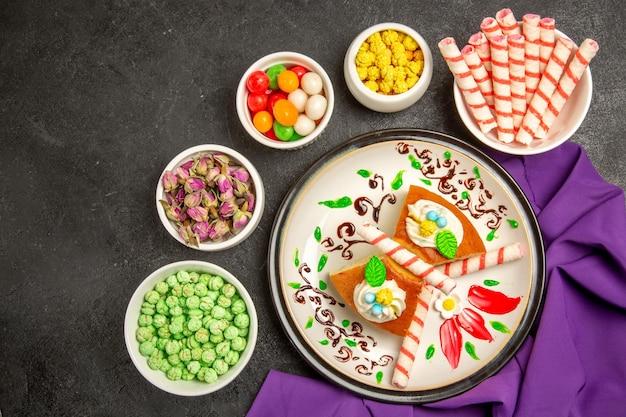 Fette di torta cremosa vista dall'alto con tessuto viola e caramelle su spazio grigio