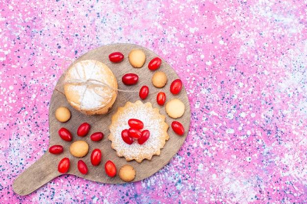 Vista dall'alto di biscotti sandwich cremosi con cornioli rossi su bacche di frutta dolce e acide luminose, biscotti torta biscotto