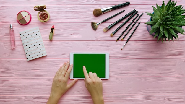 Top view of creative composition with cosmetics, makeup tools, accessory and woman hands using tablet on color surface. beauty and fashion concept.
