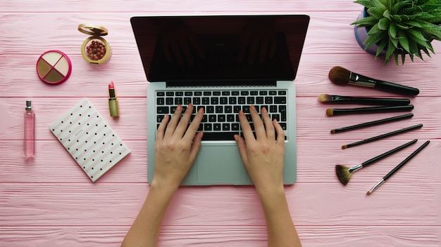 Top view of creative decorated composition with cosmetics, makeup tools, accessory and woman hands using laptop on color surface. beauty, fashion and shopping concept.