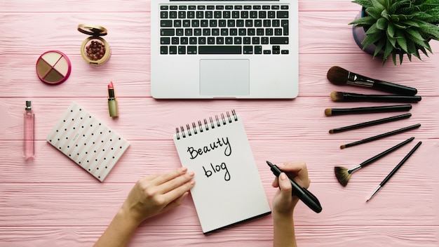Top view of creative decorated composition with cosmetics, makeup tools, accessory and woman hands writing on notebook on color surface. beauty, fashion and shopping concept.