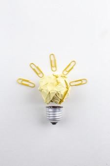 Вид сверху творческой идеальной лампочки, сделанной из бумажных зажимов с драгоценными камнями на белом столе