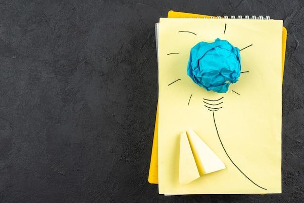 Vista dall'alto idea creativa lampadina sull'aereo di carta del blocco note su sfondo nero