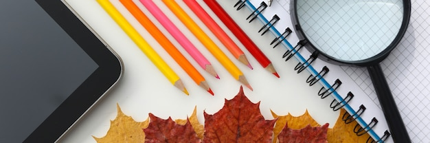 Top view of creative space with tablet magnifying glass notebook colourful pencils and autumn leaves as decoration