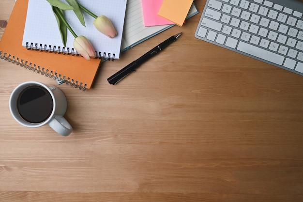 Вид сверху творческое рабочее место с тетрадью, запиской, кофейной чашкой, клавиатурой и ручкой на деревянном фоне.