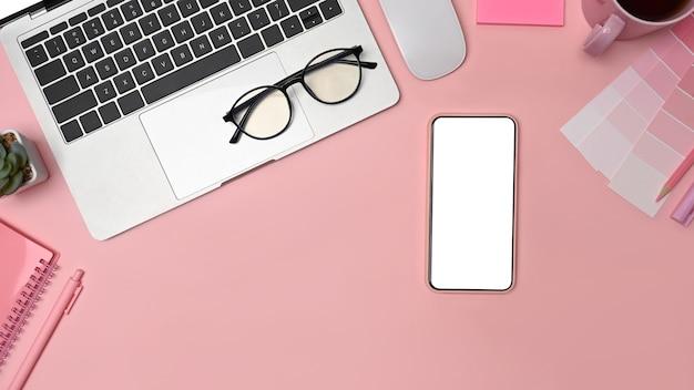 Творческое рабочее пространство с видом сверху, ноутбуком, ноутбуком, смартфоном и образцом цвета.