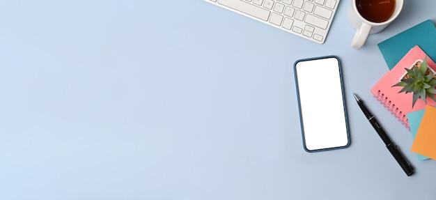 青い背景にスマートフォン、付箋、コーヒーカップ、ノートブックを備えたトップビューのクリエイティブなワークスペース。