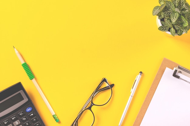 Top view of creative workspace with stationery supplies on yellow background. flat lay sty