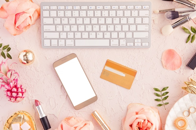 Top view of credit card and mobile phone with blank screen, online shopping and payment concept, female pastel pink workspace with flowers and laptop