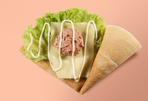 Top view of crepe or fine pancake with tuna, lettuce, cheese and mayonnaise on a salmon and coral colored background.